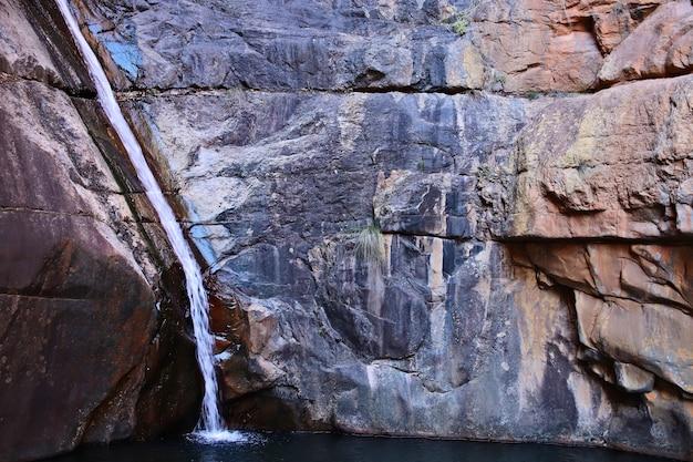 Wasserfall fließt durch eine felsformation und strömt in den fluss