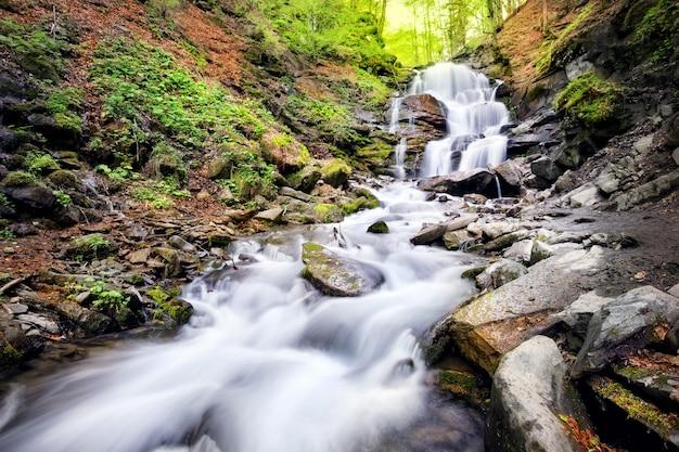 Wasserfall in felsen zwischen bäumen