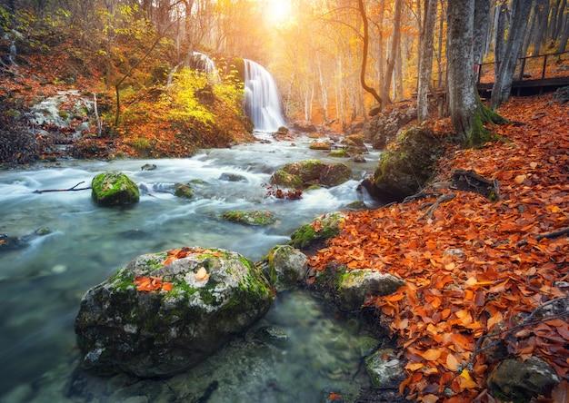 Wasserfall in gebirgsfluss im herbstwald bei sonnenuntergang.