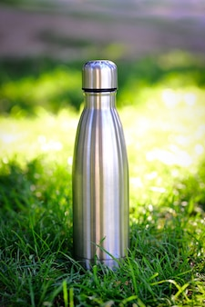 Wasserflasche auf dem hintergrund von verschwommenem gras mit kopienraum textfreiraum vertikales foto