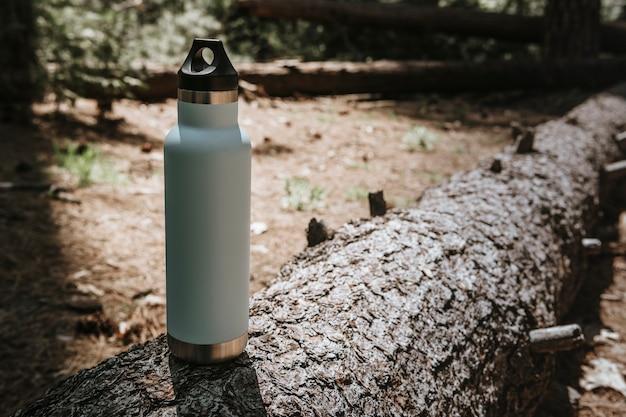 Wasserflasche auf einem baumstamm in einem wald