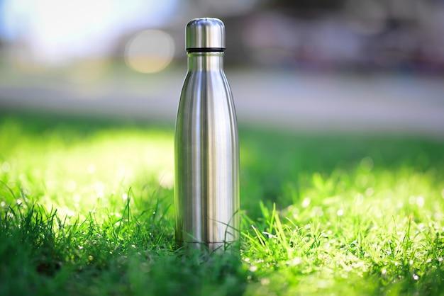 Wasserflasche auf grünem gras stahl-thermowasserflasche aus silber auf dem hintergrund von verschwommenem gras