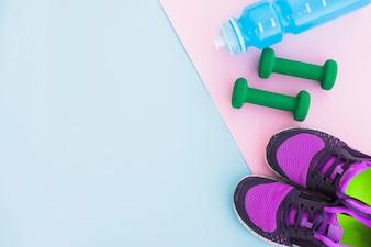 Wasserflasche; Sportschuhe und Hanteln auf rosa Hintergrund auf blauem Hintergrund