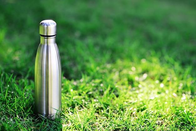 Wasserflasche wiederverwendbare stahlthermowasserflasche auf grünem gras