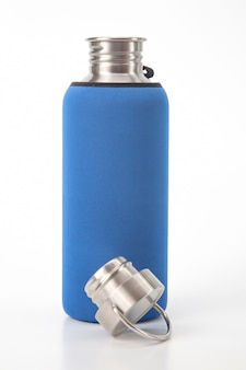 Wasserflaschen aus metallstahl an der weißen wand. metalltrinkutensilien