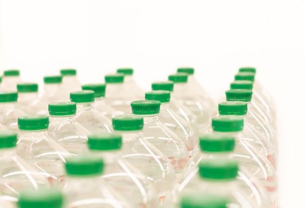 Wasserflaschen mit grünen plastikkappen auf weißem hintergrund