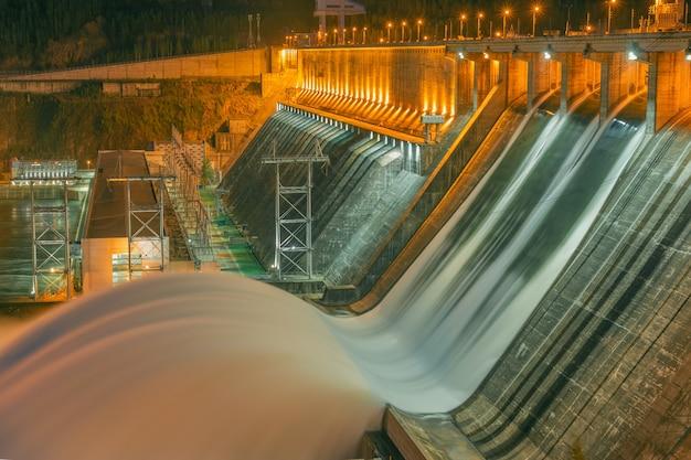 Wasserfluss, der von einem wasserkraftwerk abgegeben wird. beleuchtung des wasserflusses.