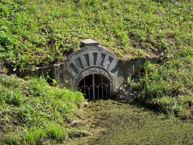 Wasserfluss im teich. der eingang ist durch einen starken metallgrill verschlossen.