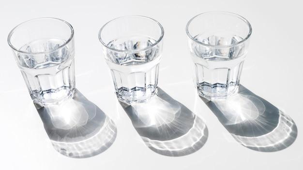 Wassergläser mit glänzendem sonnenlichtschatten auf weißem hintergrund