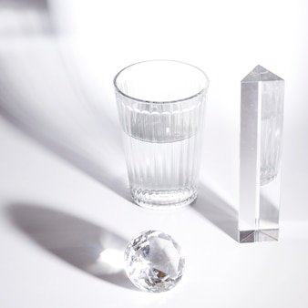 Wasserglas; kristalldiamant und prisma mit starken schatten auf weißem hintergrund