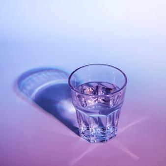 Wasserglas mit dunklem schatten auf blauem und rosa hintergrund