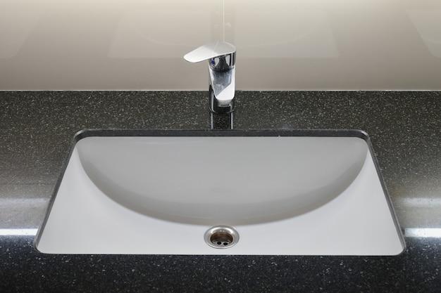 Wasserhahn im modernen stil mit schwarzer granitplatte