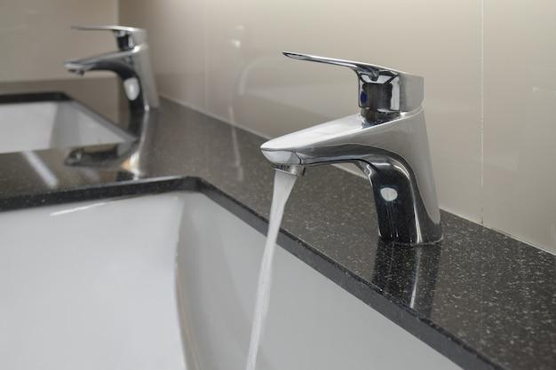 Wasserhahn im modernen stil mit unterbauwaschbecken in der toilette