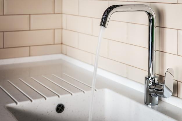 Wasserhahn in der küche. wasser fließt aus dem wasserhahn
