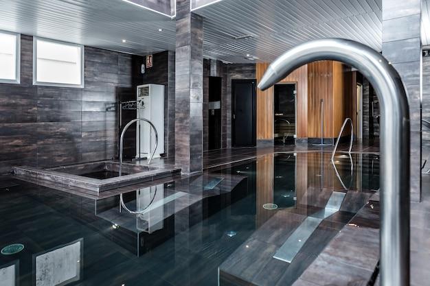 Wasserhahn in der nähe des pools im spa-salon