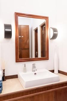 Wasserhahn oder wasserhahn mit waschbecken und spiegel im badezimmer