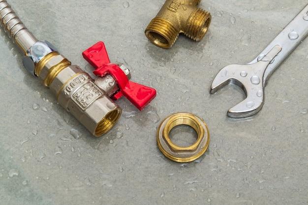 Wasserhahn und schraubenschlüssel in wassertropfen