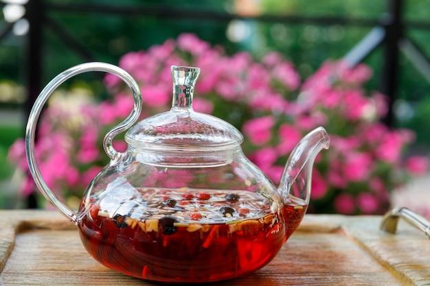 Wasserkocher aus glas mit tee steht auf einem tablett in der natur. foto in hoher qualität