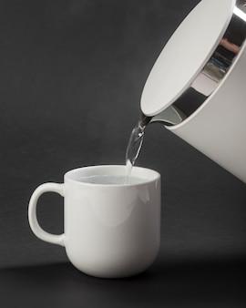 Wasserkocher, der wasser in tasse gießt