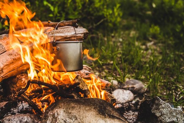Wasserkocher hängt an einem ast über dem feuer