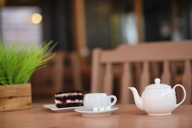 Wasserkocher mit einem getränk und dessert im straßencafé. tee in der wasserkochertasse auf dem tisch. frühstück mit tee und kuchen im café.