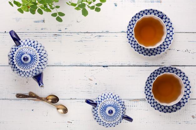 Wasserkocher mit frischem tee und einer keramikschale auf dem tisch. keramik-teeservice mit künstlerischer malerei.