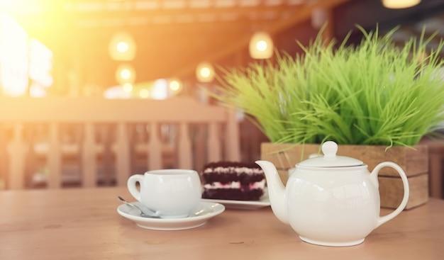 Wasserkocher mit getränk und dessert im straßencafé. tee in der wasserkochertasse auf dem tisch. frühstück mit tee und kuchen im café.