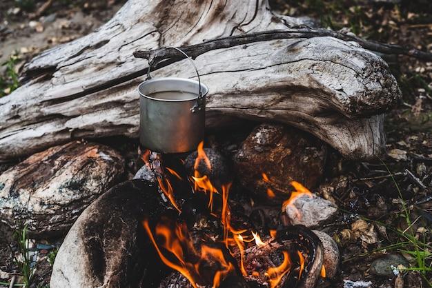 Wasserkocher über feuer hängen.
