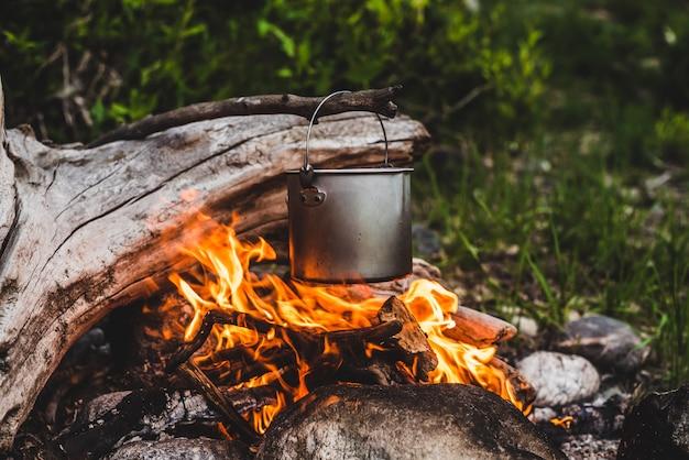 Wasserkocher über feuer im wald hängen
