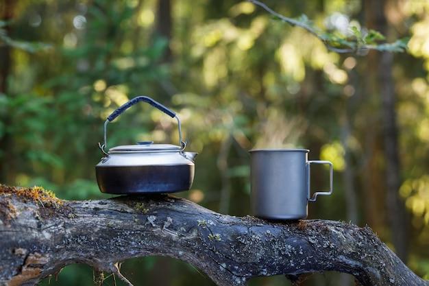 Wasserkocher und eine titantasse tee auf einem baumstamm im wald. hintergrund ist unscharf.