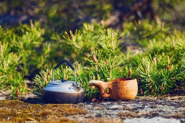 Wasserkocher und holztasse mit leckerem kaffee auf einem granitfelsen auf einem hintergrund der kiefer. der hintergrund ist verschwommen.