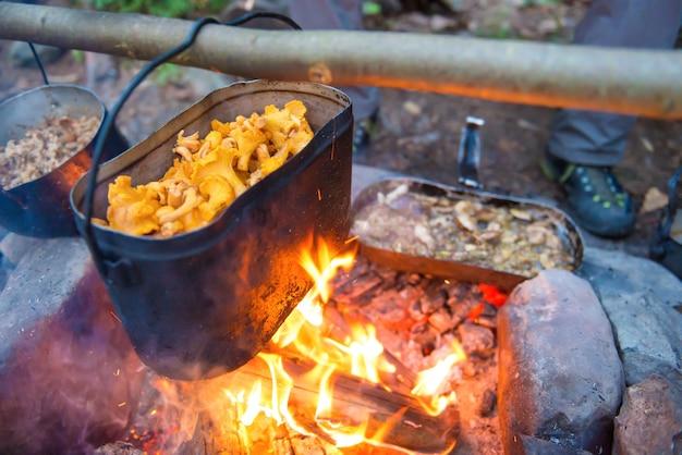 Wasserkocher voller pilze auf dem feuer