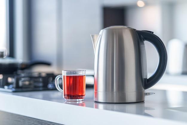 Wasserkocher zum kochen von wasser und zum zubereiten von tee auf einem tisch im kücheninneren. haushaltsküchengeräte für macht heiße getränke