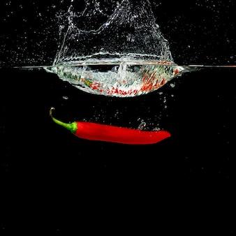 Wasserkronen-spritzenform durch den roten paprika, der in wasser fällt