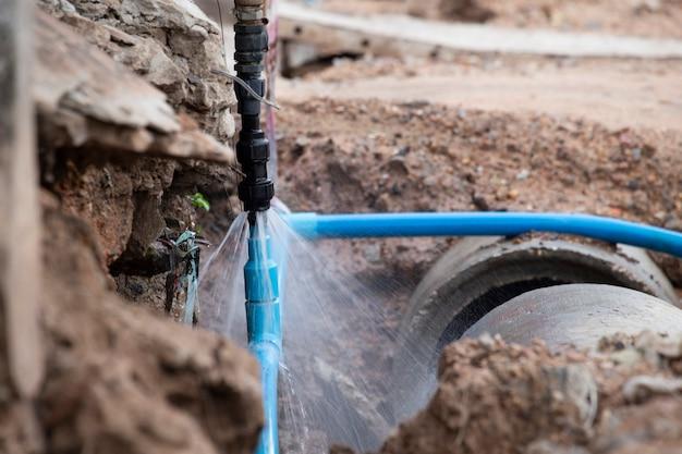 Wasserleitungsbruch. freilegen einer geplatzten wasserleitung, die sich auf das sprühwasser und das rohr konzentriert.
