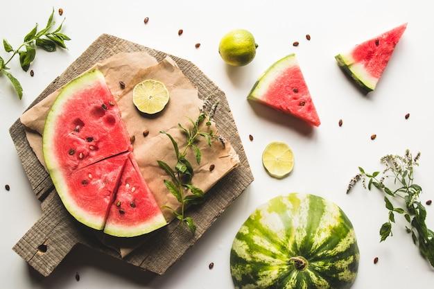 Wassermelone auf einem geschnittenen brett mit minze und limettenscheiben. lebensmittel