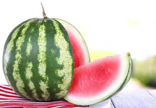 Wassermelone auf serviette auf ständer auf holztisch auf natürlichem hintergrund