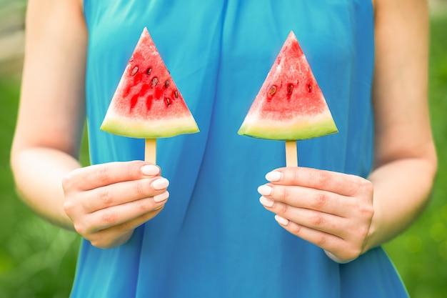 Wassermelone auf zwei stöcken in ihren händen des weibchens auf einem blauen kleidhintergrund.