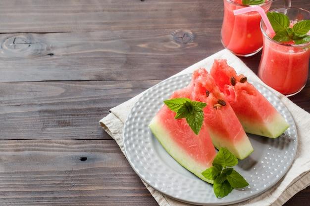 Wassermelone geschnitten auf einer platte mit tadellosen blättern und frischem wassermelone smoothie