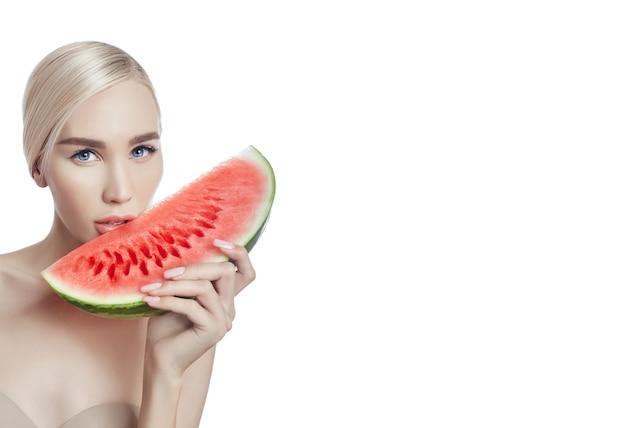Wassermelone in den händen von frauen, säubern sie glatte haut des körpers und des gesichtes. blondes mädchen