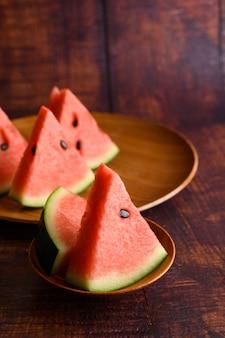 Wassermelone in stücke geschnitten in einer schüssel auf einem holztisch.