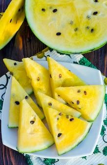 Wassermelone mit gelbem fruchtfleisch. geschnittene beerenstücke auf einem holztisch.