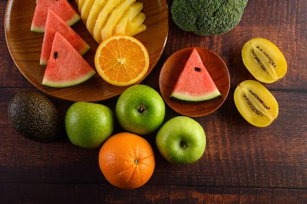 Wassermelone, orange, ananas, kiwi in scheiben geschnitten mit äpfeln und brokkoli auf einem holzteller und holztisch.