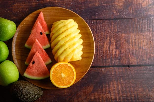 Wassermelone, orange und ananas auf einem holzteller mit äpfeln in stücke geschnitten.