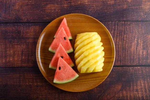 Wassermelone und ananas auf einem holzteller in stücke geschnitten
