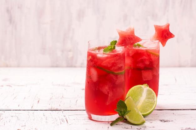 Wassermelone und kalk frisch in den hohen gläsern, die durch wassermelone verziert werden, spielen auf weißem holztisch die hauptrolle