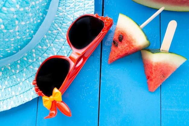 Wassermelone und schwarze gläser in der blauen tabelle auf hintergrund des blauen hutes,