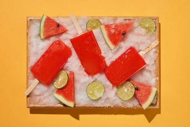Wassermelonen-eis am stiel und geschnittene zitrone auf einem mit eis gefüllten tablett