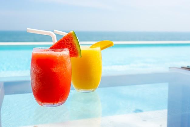 Wassermelonen-smoothie und mango-smoothie mit swimmingpool und meer