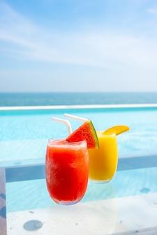 Wassermelonen-smoothie und mango-smoothie mit swimmingpool und meeresstrand